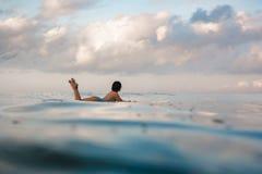 Mujer joven en el bikini brillante que practica surf en un tablero en el océano Fotos de archivo libres de regalías