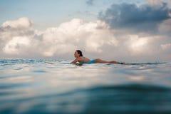 Mujer joven en el bikini brillante que practica surf en un tablero en el océano Foto de archivo
