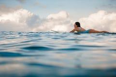 Mujer joven en el bikini brillante que practica surf en un tablero en el océano Imagen de archivo libre de regalías