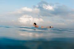 Mujer joven en el bikini brillante que practica surf en un tablero en el océano Imagen de archivo