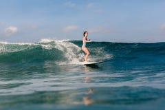 Mujer joven en el bikini brillante que practica surf en un tablero en el océano Fotografía de archivo