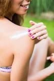 Mujer joven en el bikini que aplica la protección solar Foto de archivo libre de regalías