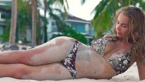 Mujer joven en el bikini que miente en la playa del mar y que derrama la arena en su cuerpo Arena de la mujer atractiva que juega almacen de video