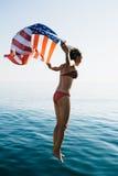 Mujer joven en el bikini que salta en agua con la bandera americana fotografía de archivo libre de regalías