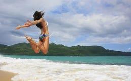 Mujer joven en el bikini que salta en la playa de Rincon, península de Samana Imagenes de archivo