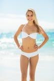 Mujer joven en el bikini que se coloca en la playa Foto de archivo libre de regalías