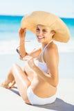 Mujer joven en el bikini que se sienta en la playa Imagen de archivo