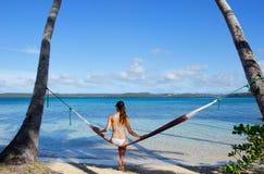 Mujer joven en el bikini que se sienta en una hamaca entre las palmeras Imagen de archivo libre de regalías