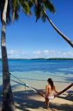 Mujer joven en el bikini que se sienta en una hamaca entre las palmeras, O Imagen de archivo
