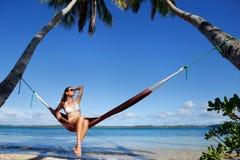Mujer joven en el bikini que se sienta en una hamaca entre las palmeras, O Fotos de archivo libres de regalías