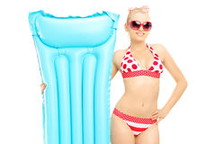 Mujer joven en el bikini que sostiene un colchón de la natación Imagenes de archivo