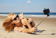 Mujer joven en el bikini que toma la foto del selfie con el palillo en el beac Foto de archivo
