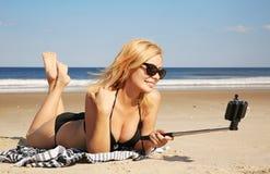 Mujer joven en el bikini que toma la foto del selfie con el palillo en el beac Fotos de archivo libres de regalías