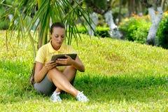 Mujer joven en el césped debajo de una palmera con su comput de la tableta Fotos de archivo libres de regalías