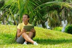 Mujer joven en el césped debajo de una palmera con su comput de la tableta Foto de archivo
