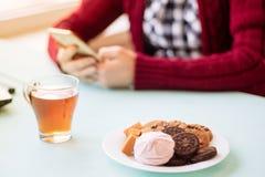 Mujer joven en el café que bebe y que usa el teléfono móvil adentro el domingo por la mañana Foto de archivo libre de regalías
