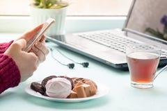 Mujer joven en el café que bebe y que usa el teléfono móvil en domingo MES Foto de archivo libre de regalías