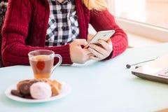 Mujer joven en el café que bebe y que usa el teléfono móvil en domingo MES Fotos de archivo libres de regalías