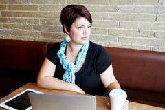 Mujer joven en el café que mira hacia fuera la ventana Imágenes de archivo libres de regalías