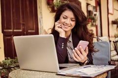 Mujer joven en el café usando el teléfono elegante, negocio Fotos de archivo