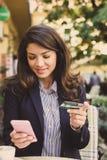 Mujer joven en el café usando el teléfono elegante para comprobar la tarjeta de crédito Imagen de archivo