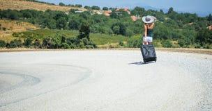 Mujer joven en el camino con equipaje Foto de archivo libre de regalías