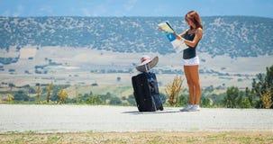 Mujer joven en el camino con equipaje y el mapa Imagen de archivo