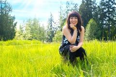 Mujer joven en el campo de la hierba imagen de archivo