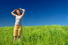 Mujer joven en el campo verde Imagenes de archivo
