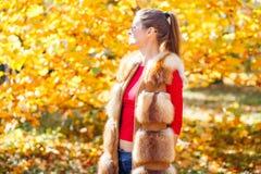 Mujer joven en el chaleco de la piel que presenta en parque del otoño Foto de archivo