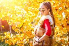 Mujer joven en el chaleco de la piel que presenta en parque del otoño Imagenes de archivo
