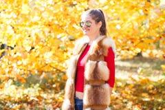 Mujer joven en el chaleco de la piel que presenta en parque del otoño Fotos de archivo libres de regalías
