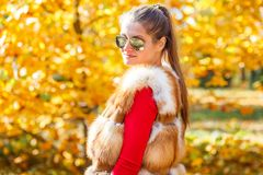 Mujer joven en el chaleco de la piel que presenta en parque del otoño Fotografía de archivo libre de regalías