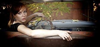 Mujer joven en el coche viejo Foto de archivo libre de regalías