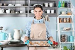 Mujer joven en el delantal que sostiene la bandeja de la hornada con las galletas imagen de archivo libre de regalías