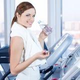 Mujer joven en el ejercicio de la gimnasia. Bebida Foto de archivo