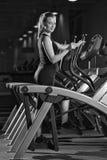 Mujer joven en el ejercicio de la gimnasia Corra en la máquina Fotografía de archivo