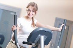 Mujer joven en el ejercicio de la gimnasia. El ejecutarse Imagenes de archivo