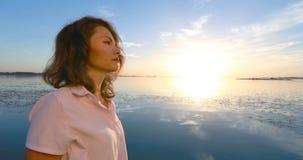 Mujer joven en el embarcadero por el río en la puesta del sol metrajes