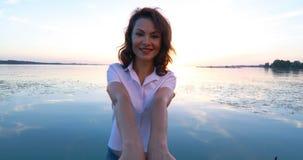 Mujer joven en el embarcadero por el río en la puesta del sol almacen de metraje de vídeo