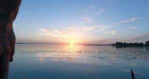 Mujer joven en el embarcadero por el río en la puesta del sol almacen de video