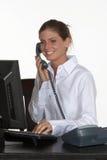 Mujer joven en el escritorio que habla en el teléfono Fotografía de archivo libre de regalías