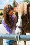 Mujer joven en el establo con el caballo en la sol Fotos de archivo