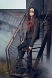 Mujer joven en el estilo industrial que se coloca en las escaleras Fotografía de archivo libre de regalías