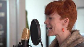 Mujer joven en el estudio para registrar una etiqueta de la voz para los proyectos comerciales en el micrófono del estudio almacen de metraje de vídeo