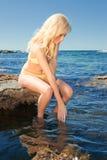 Mujer joven en el filón en el mar Imagenes de archivo