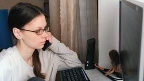 Mujer joven en el funcionamiento de vidrios en el ordenador y el teléfono móvil de discurso metrajes