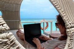 Mujer joven en el funcionamiento del traje de baño en un ordenador durante día de fiesta Agua tropical azul clara como fondo foto de archivo