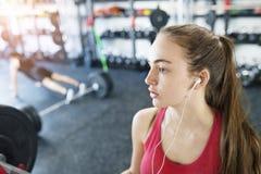 Mujer joven en el gimnasio, auriculares en sus oídos, música que escucha Imagen de archivo libre de regalías