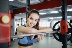 Mujer joven en el gimnasio usando el equipo de la aptitud Foto de archivo libre de regalías